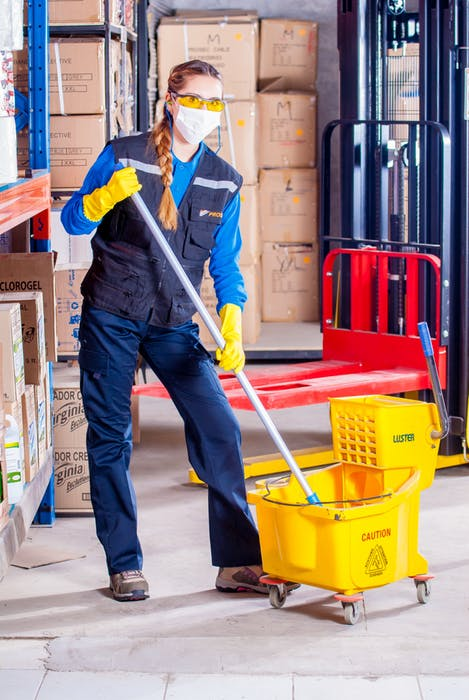 woman in cleaning uniform while mopping the floor